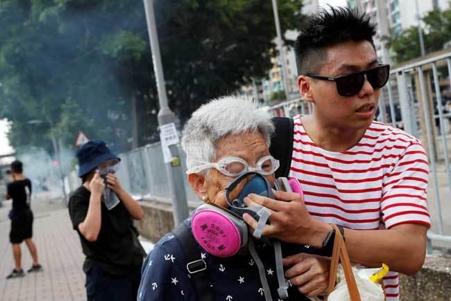 香港で警察が放った催涙ガスから身を守るよう通行人を助けるデモ参加者