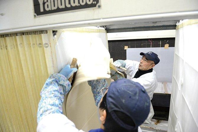 搾りの際の酒粕を剝がす作業。奥が、杜氏の石川達明さん
