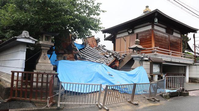 大阪北部地震でひっくり返った浄教寺の門。雨に備えてブルーシートがかけられていた