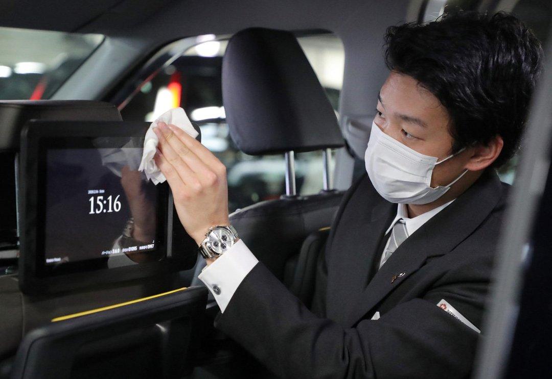 新型コロナウイルスの感染予防対策で、タクシー車内の消毒を行う担当者(2月16日撮影)