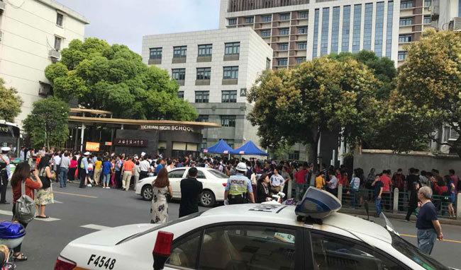 入試開場前に群がる受験生の両親や親戚、それを見守る警察官。