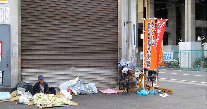 あいりん労働福祉センターの外で寝泊まりするホームレス男性