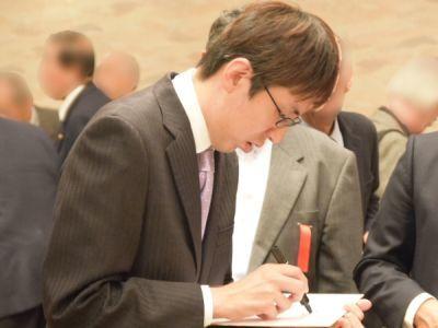 サインを書く広瀬章人氏