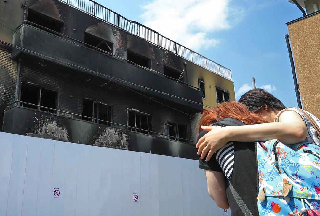放火された「京都アニメーション」第1スタジオの前で涙ぐむ女性ら=25日、京都市伏見区