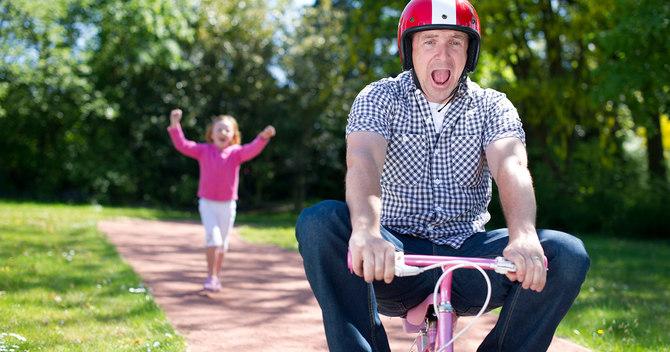 娘の自転車に乗る父親