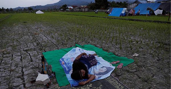 ロンボク島北部で7日、屋外で休憩する被災女性