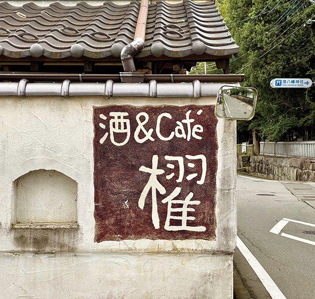 カフェの看板の奥は鎮守の森