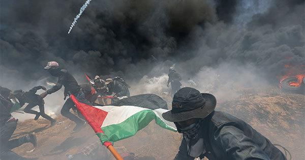 イスラエル軍の催涙ガスなどから逃げるパレスチナ人抗議活動参加者