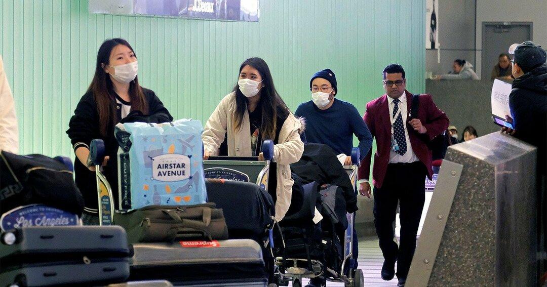 マスク姿で移動する旅客