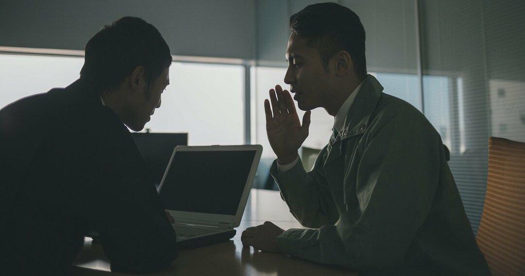 内緒話をする男性2人のイメージ写真