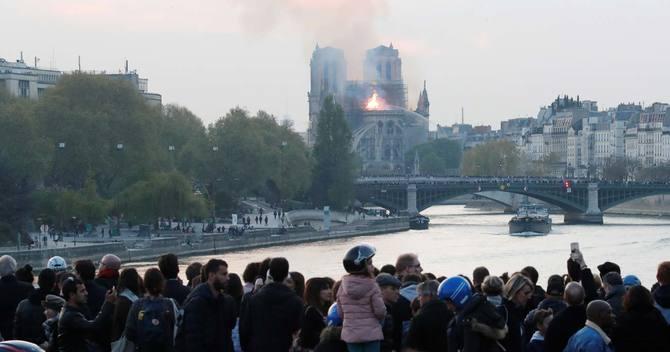 ノートルダム寺院の火災を見つめる市民ら