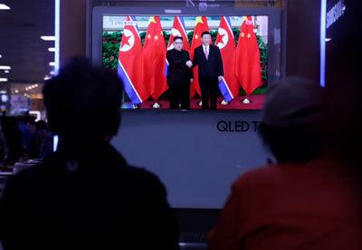 5月、韓国ソウルでTVニュースを眺める人々