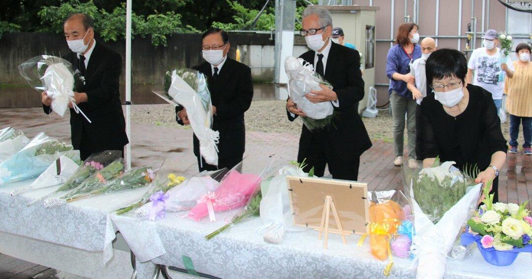 障害者施設「津久井やまゆり園」前に設置された献花台で、花を供える参列者(7月26日撮影)