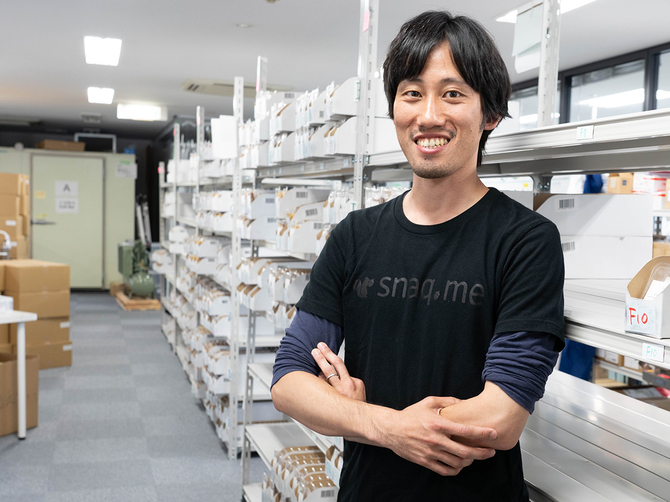 スナックミー代表取締役の服部慎太郎氏。オフィスにはボックスに詰める前のお菓子が並ぶ PhotobyYuheiIwamoto