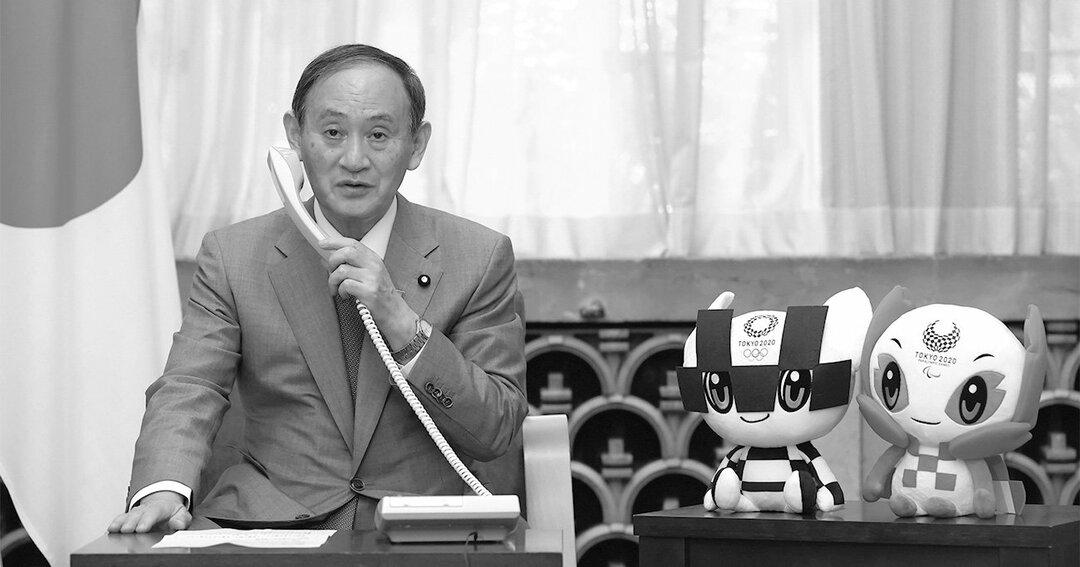 東京五輪柔道男子60キログラム級で金メダルを獲得した高藤直寿と電話で話す首相の菅義偉。人気取りのための行為と映り、内閣支持率の回復にはつながっていないようだ[代表撮影]