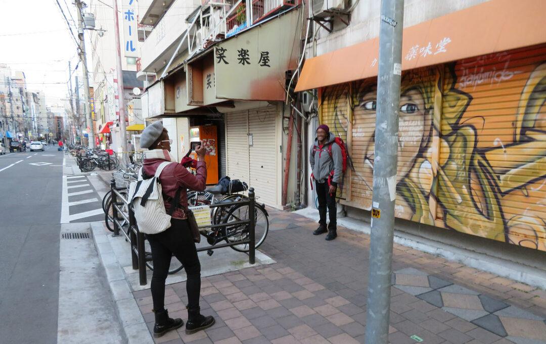 カレー店「薬味堂」のシャッター前で記念撮影する外国人観光客。今や、西成は、「日本のハーレム」として外国人観光客の間で認知が進みつつあるようだ