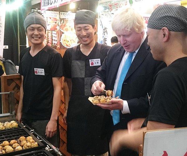 大阪・道頓堀でたこ焼きをほおばるジョンソン首相(2015年当時はロンドン市長)。 (出所) 英国大使館国際通商部公式ツイッター