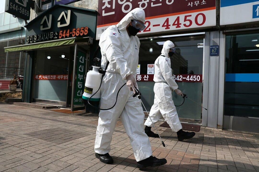 韓国・ソウル市で消毒剤を撒く防護服姿の韓国軍兵士(3月9日撮影)