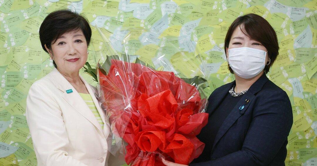 東京都知事選で当選確実となり、花束を贈られる小池百合子氏(左)=5日午後、東京都新宿区