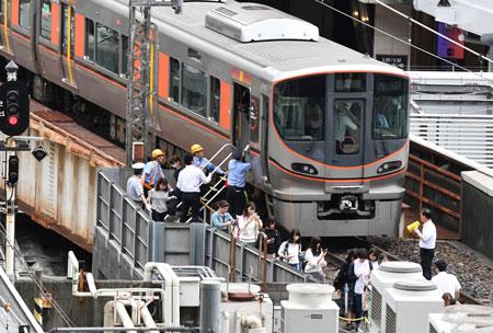 大阪北部地震で係員に誘導されて電車から避難する人々