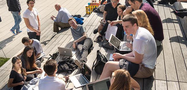 パソコンを持って集まる若者