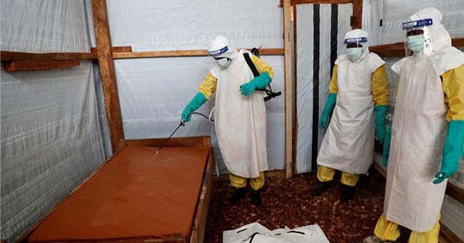 エボラでの死亡が疑われる乳幼児のベッドを消毒する医療従事者