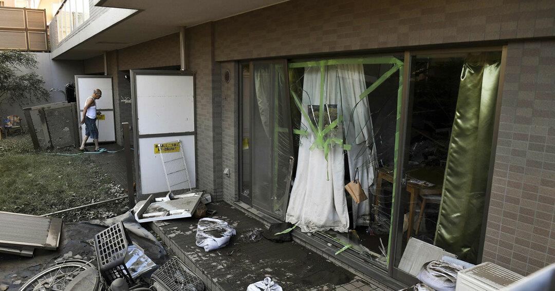 台風19号が通過した東京で壊れた住宅を掃除する男性